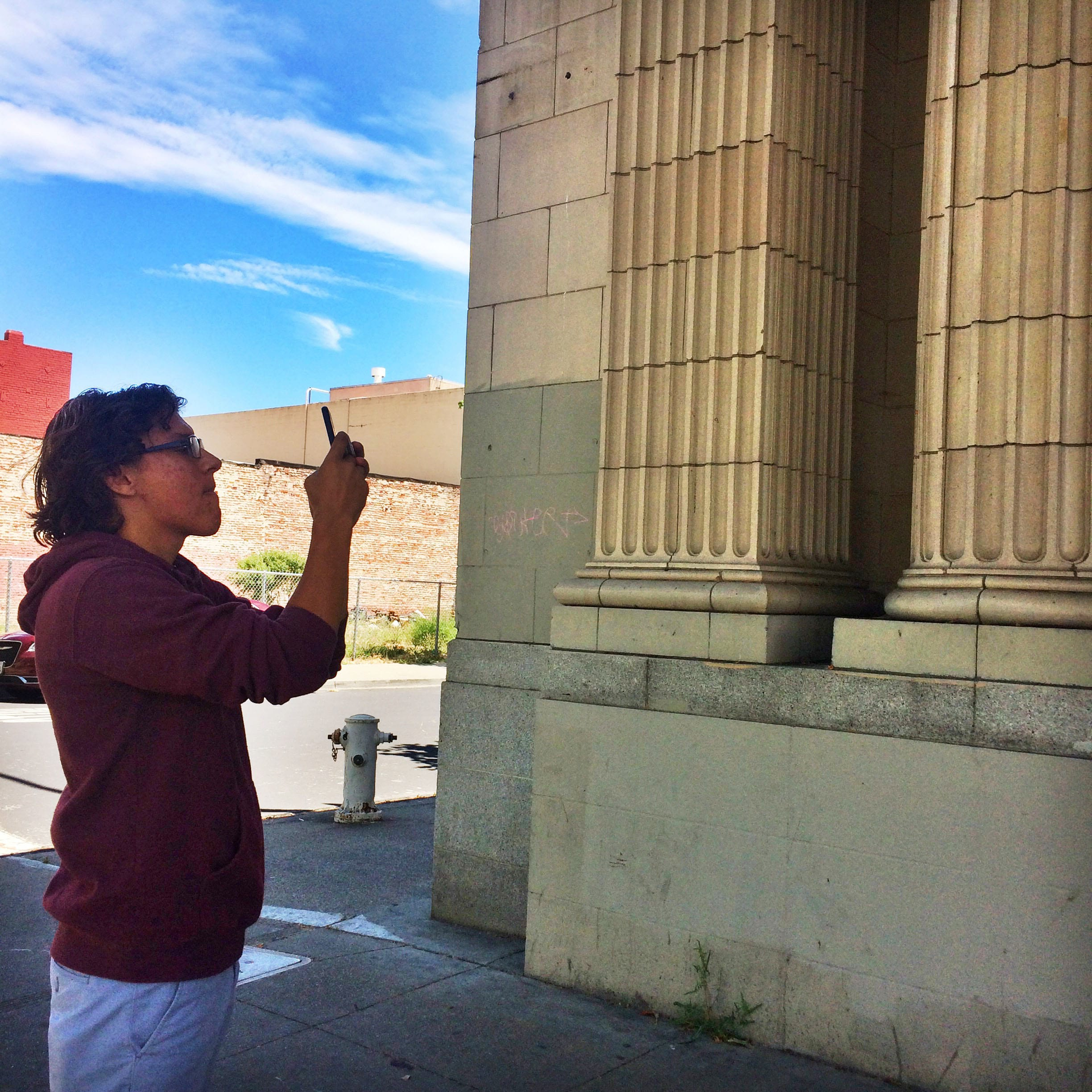 Julio photographing the historic Mechanis Bank building while touring Downtown's public art