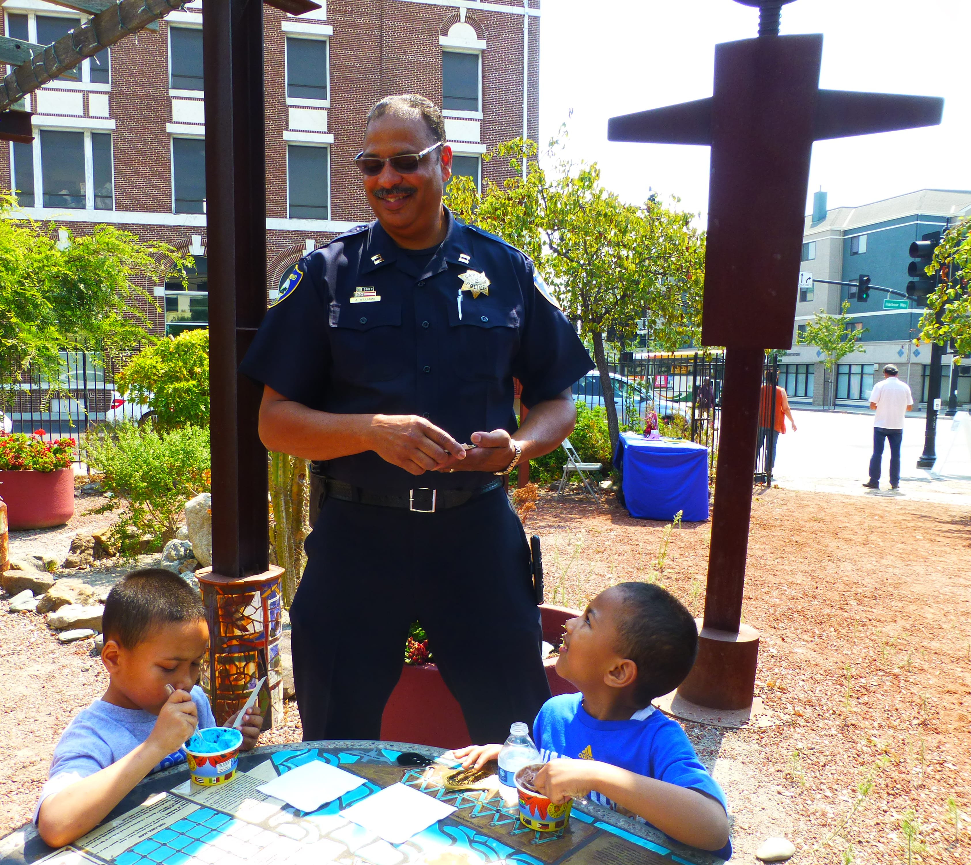 Captain Williams (former) chatting with two boys enjoying ice cream at Chill with a Cop