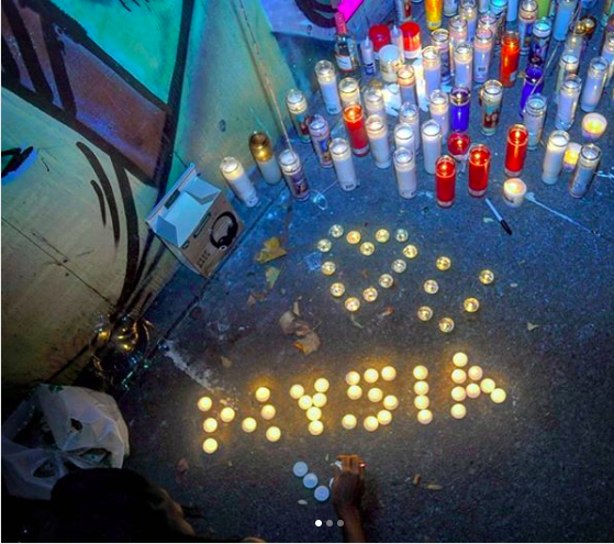 """A woman lights candles spelling """"Nysia"""" at a vigil for Vennysia Jackson on 8/14/2018. Photo by Denis Perez"""
