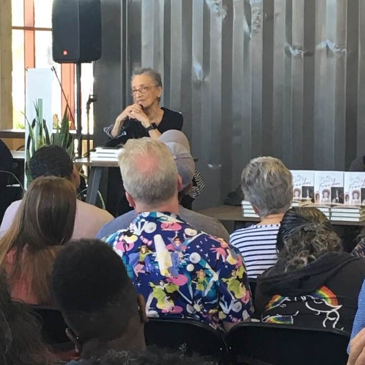 Author and activist Betty Reid Soskin speaking at the dais with copies of her book and audience in the foreground.